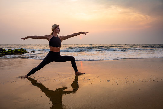 Middle age woman in black doing yoga on sand beach