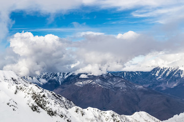 The snow capped mountains are covered with thick clouds