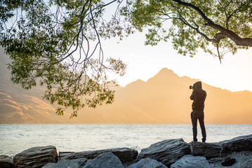 Young male photographer looking at scenery of Lake Wakatipu during golden hour sunset in Queenstown, South island, New Zealand, travel and landscape photography concepts