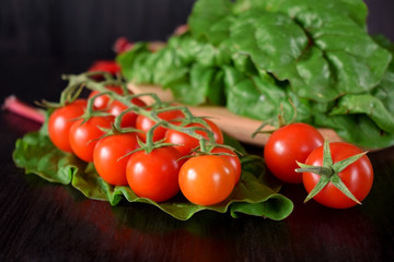 Cherry tomatoes on a dark table. Chard leaves in the background