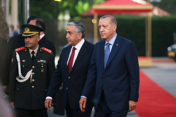 Turkish President Tayyip Erdogan and Turkish Cypriot leader Mustafa Akinci review a guard of honour during a visit in the Turkish Cypriot northern part of the divided city of Nicosia
