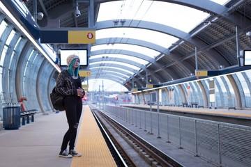 Woman waiting for a train at railway platform