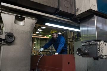 Technician in protective workwear cutting metal