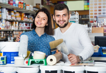 Couple purchasing tools for house improvements in paint supplies store