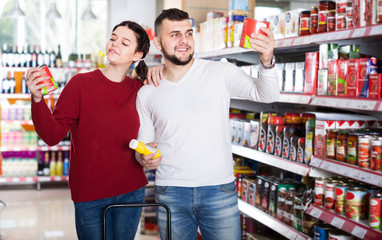 young couple choosing purchasing canned food for week at supermarket
