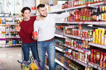 attentive couple choosing purchasing canned food for week at supermarket