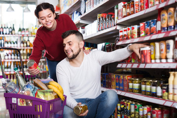 vigorous couple choosing purchasing canned food for week at supermarket