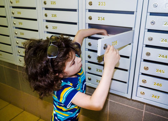 Waiting for delivery. Little boy, smart casual, at the mailboxes post, checking the mail