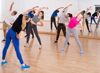 Teenage boys and girls with trainer stretching in dance hall