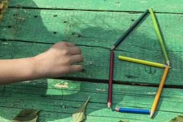 the child draw picture with colorful pens and flowers on the wooden green table in the nursery or school for activity concept. creative ideas for child development.