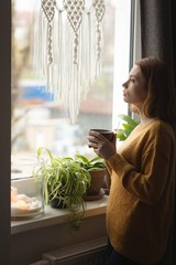 Woman having coffee while looking through window