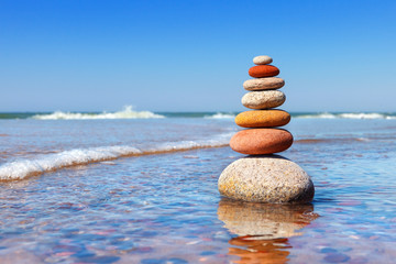 Obraz Rock zen pyramid of colorful pebbles standing in the water on the background of the sea. Concept of balance, harmony and meditation. - fototapety do salonu