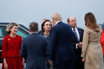 U.S. President Donald Trump and first lady Melania Trump greet U.S. Ambassador to NATO Kay Bailey Hutchison and U.S. Ambassador to Belgium Ronald J. Gidwitz as they arrive ahead of the NATO Summit, at Brussels Military Airport in Melsbroek