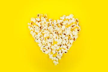 Heart shaped white fluffy popcorn on yellow background