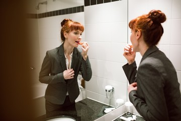 Businesswoman applying lipstick in bathroom