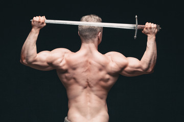 Bodybuilder man posing with a sword isolated on black background. Serious shirtless man demonstrating his mascular body. sword for head