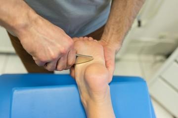Physiotherapist giving leg massage to woman