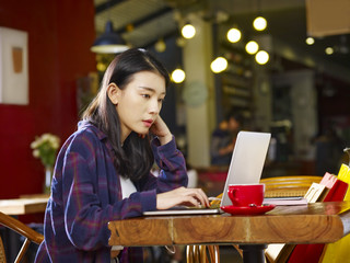 young asian woman using laptop in coffee shop