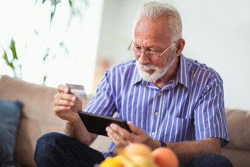 Senior man with credit card for online banking or shopping