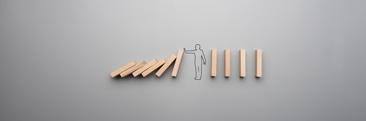 Wide cropped image of the outline of a businessman stopping the domino