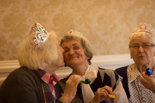 Senior woman kissing her senior friend during birthday