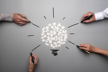 Top view of  white scattered puzzle pieces and businesspeople hands
