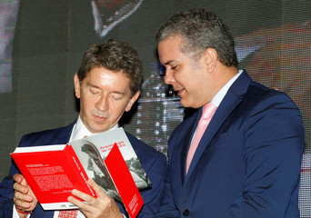 "Colombia's President-elect Ivan Duque gives a copy of his book ""Arqueologia de mi padre"" to the governor of Antioquia, Luis Perez, in Medellin, Antioquia"