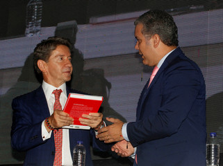"Colombia's President-elect Ivan Duque gives a copy of his book ""Arqueologia de mi padre"" to the governor of Antioquia, Luis Perez, in Medellin"