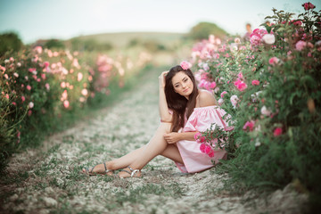 Portrait of beautiful woman is sitting in pink blossom garden. The concept of perfume advertising.