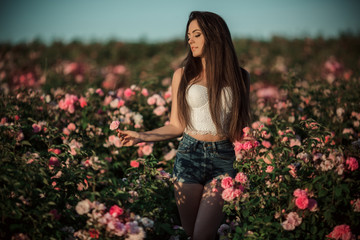 Happy smiling woman is resting in blossom garden of beautiful pink roses