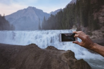 Man taking photo of waterfall with mobile phone