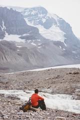 Male hiker relaxing near river