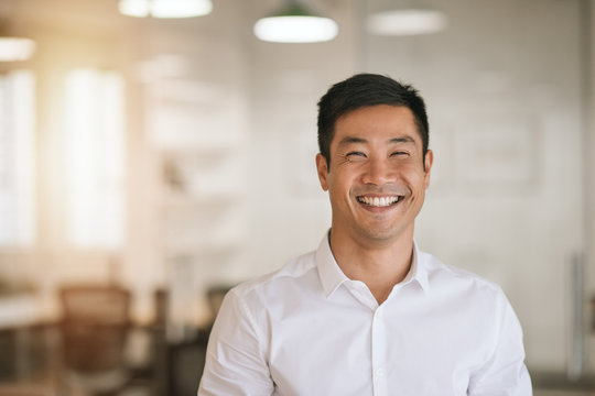 Smiling Asian businessman standing in a bright modern office