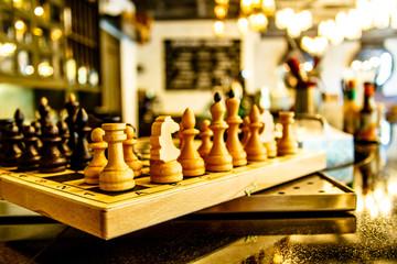 Шахматные фигуры стоят на шахматной дрске в баре или ресторане