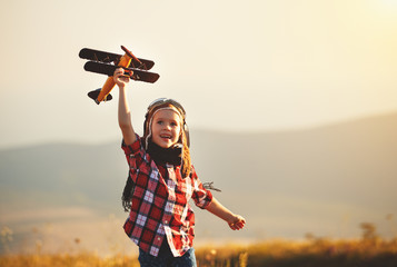 Child pilot aviator with airplane dreams of traveling in summer  at sunset