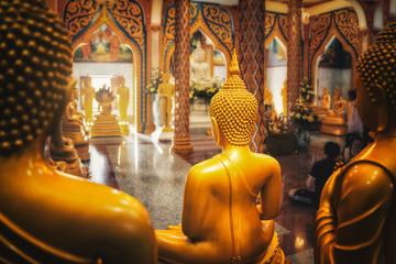 buddhist temple with golden buddha vishnu gods statue praying - phuket, thailand