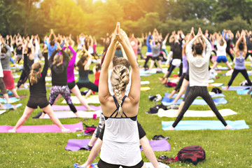 big group of adults attending a yoga class outside in park Wall mural