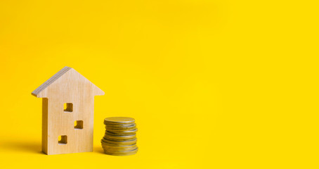 coins and wooden house on a yellow background. Concept of real estate. Buying, selling and renting a house. Loan for an apartment, mortgage rate. Affordable housing for young families.