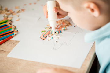 Cute little girl make applique glues colorful house, applying color paper using glue while doing arts and crafts in preschool or home. Idea for children's creativity, an art project made of paper.