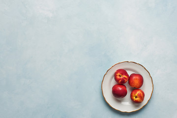 Flat lay of fresh nectarines fruits on white rustic plate on light blue background. Top view with copy space.