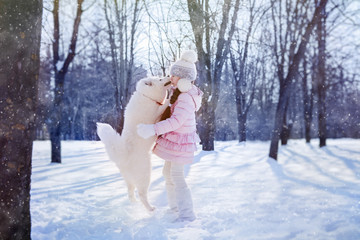 girl playing with Samoyed puppy in snow-covered park on Christmas morning.