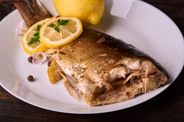 Appetizing baked fish, covered with juicy lemons, garlic and salt on side, above view