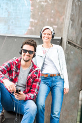 young couple listening to music in a skate park