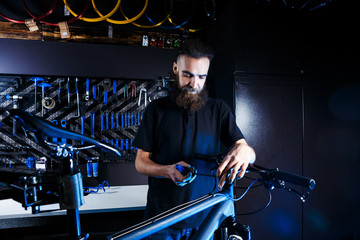 Theme sale and repair of bicycles. Young and stylish with a beard and long hair, a Caucasian man uses a tool to set up and repair a bike in a store. Business owner at work.