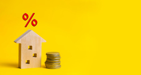 mortgage and interest on the house. buy of property, home, real estate. affordable housing. place for text. advantageous offer from the bank. Government program. wooden house on a yellow background.