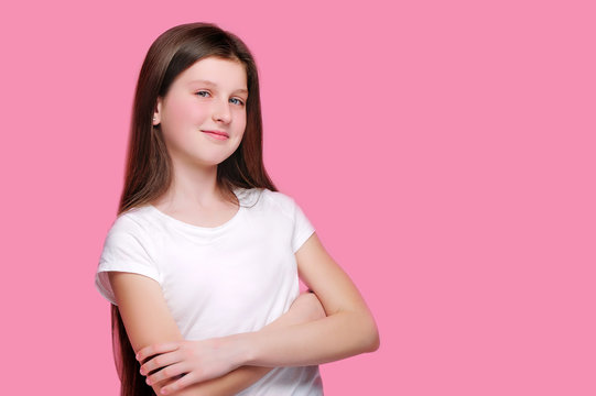 Smiling teen girl with crossed hands against pink background