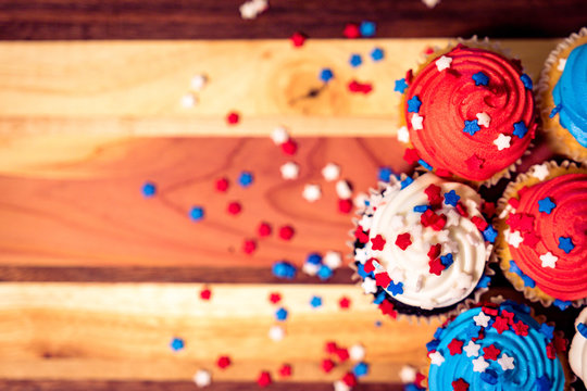 Colorful 4th of July cupcakes with star sprinkles on board