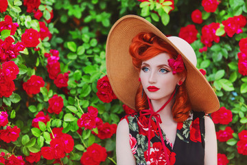 Stunning girl with red lips in dress with a print of roses on a beautiful summer background. Young redhead model in hat on a background stunning roses bush. Stylish woman. Fashionable summer clothes