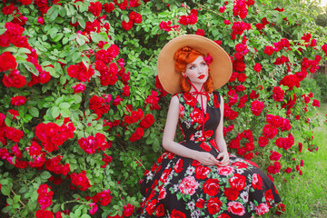 Retro girl in wondrous dress with a print of roses on a beautiful summer background. Young wondrous redhead model in hat on background of bush of roses. Stylish woman. Fashionable summer dress