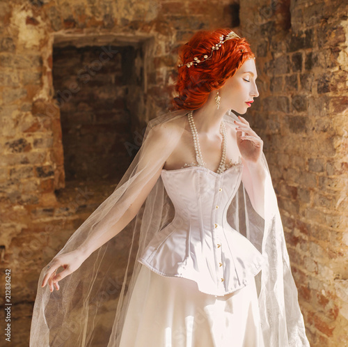 62b771c3115 Young renaissance redhead princess with hairstyle in the old castle. Fabulous  rococo queen in white